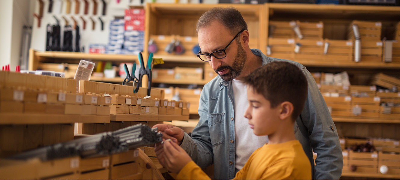 Small business owner teaching son about tools.