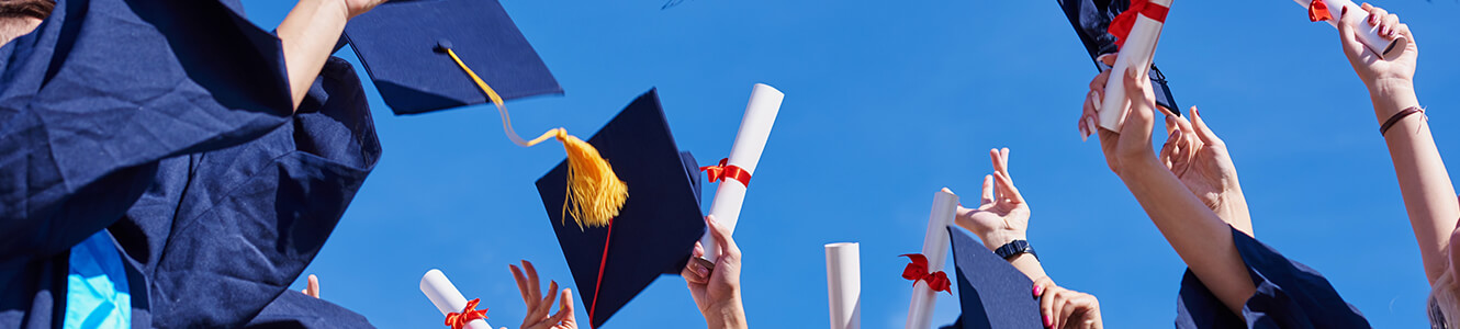 College graduates tossing their graduation hats up in the airt