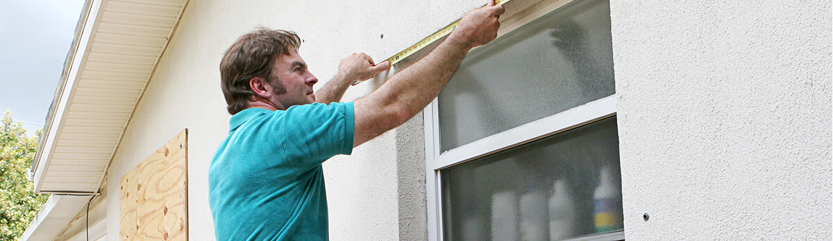 Man on a ladder, outside a home, measuring the top of a window so he can attach plywood to prepare for a hurricane.