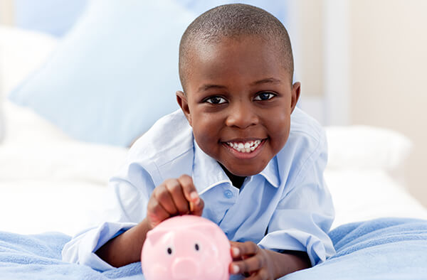 Young boy putting money in a piggy bank