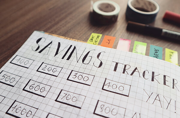 A hand drawn savings tracker on a piece of grided paper.